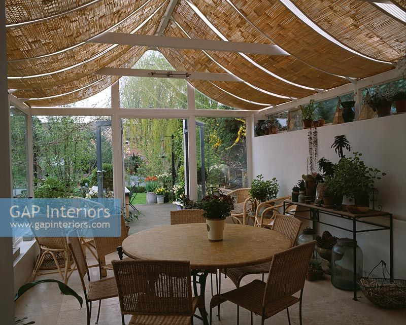 View of country conservatory with roof blinds and dining table and view to garden