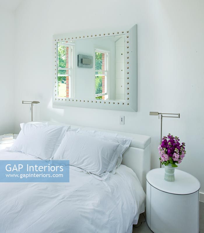 Modern White Bedroom With Mirror Above Bed And Bedside Table Vase Of Stocks