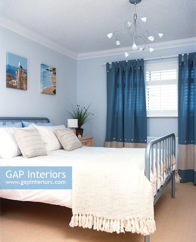 Modern bedroom with double bed  chandelier and blue curtains. GAP Interiors   Modern bedroom with double bed  chandelier and