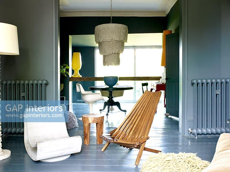 Open plan grey living and dining room with painted walls and floorboards