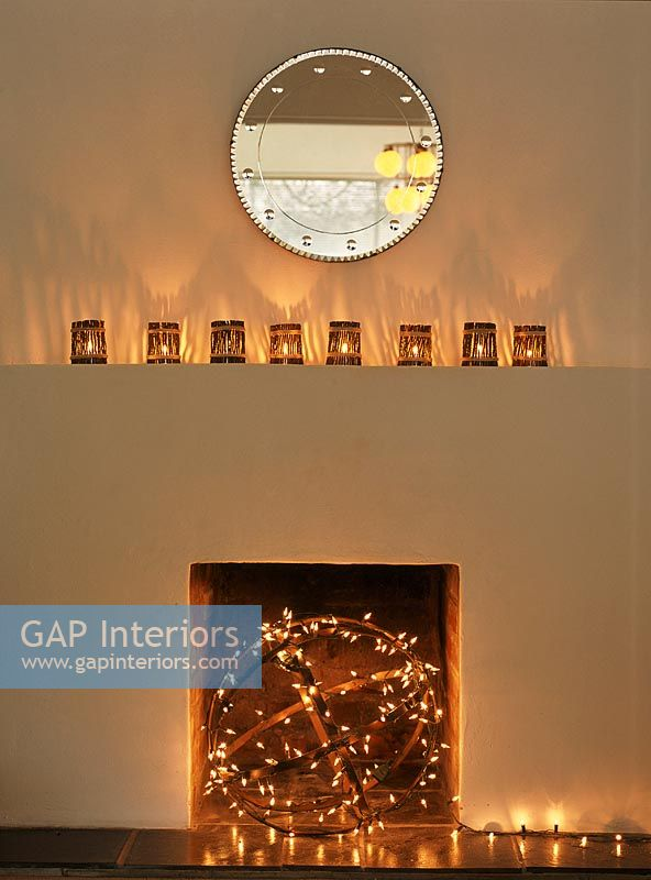 GAP Interiors Fireplace illuminated by a strand of christmas