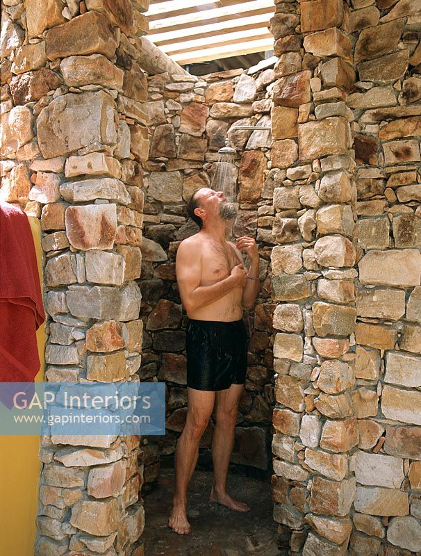 Man bathing in a stone shower