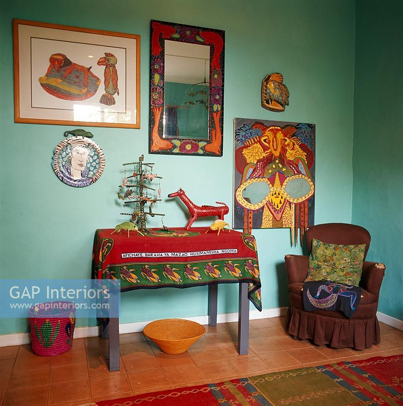 Decorated toys on side table and painting and mirror hanging on wall