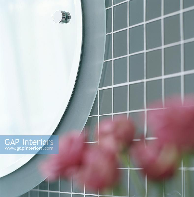 Close-up of a round bathroom mirror with out of focus flowers