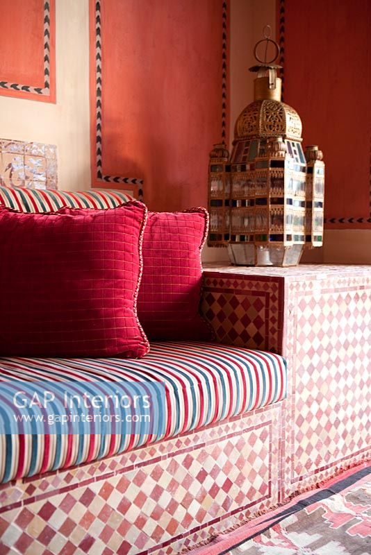 Detail of patterned moroccan sofa and brass lantern