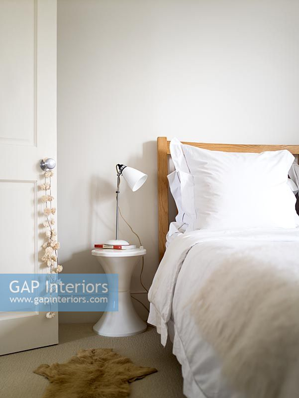 Contemporary white bedroom with Tam Tam stool used as bedside table