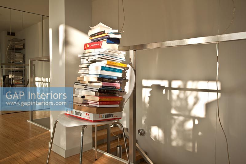 Pile of books on modern chair, detail