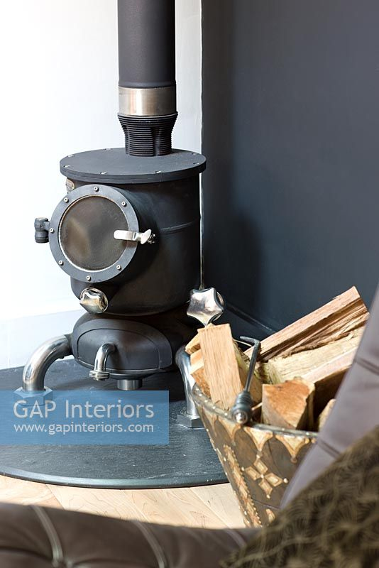Small round wood burning stove by black wall - GAP Interiors - Small Round Wood Burning Stove By Black Wall