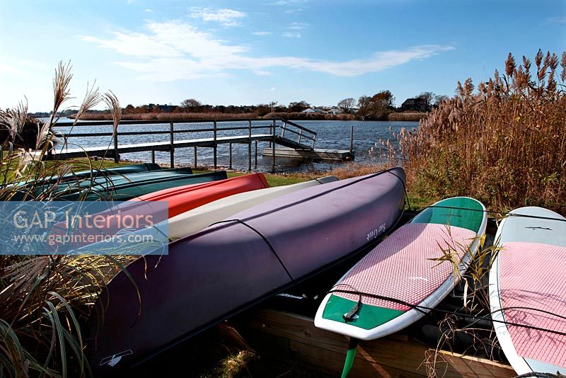Canoes and surfboards at waters edge