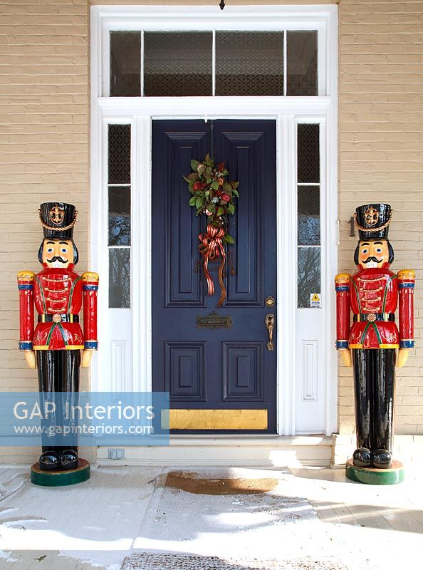 Colourful carved soldiers flanking front door