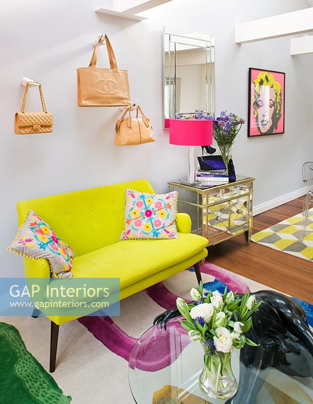 Open plan living room with designer handbags displayed on wall mounted hands