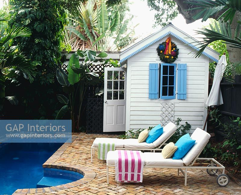 Loungers and summerhouse in tropical garden