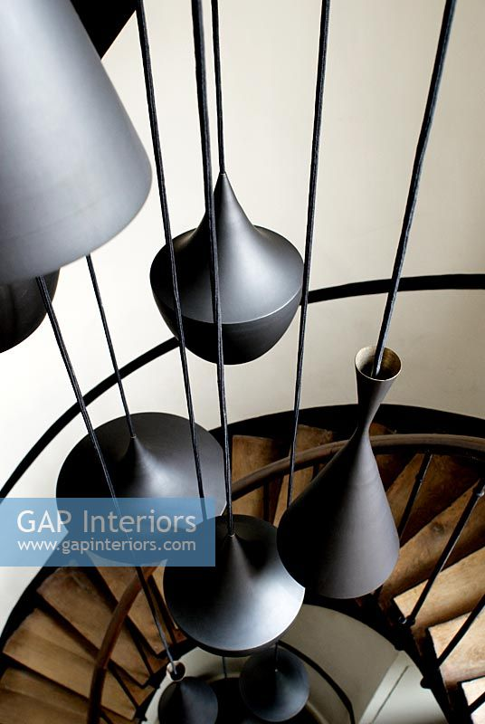 Modern pendant lights hanging over spiral staircase