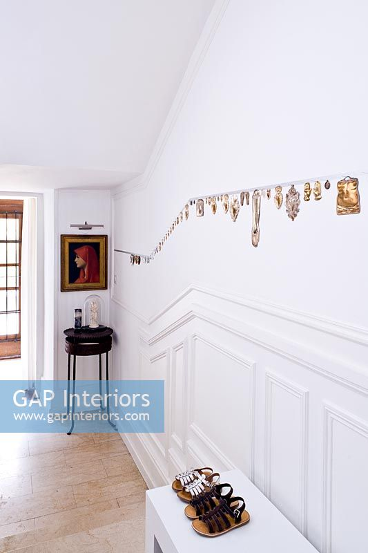 Landing with collection of votive coins on wall