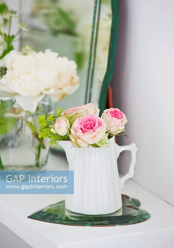 Roses and Ladys mantle flowers in white jug
