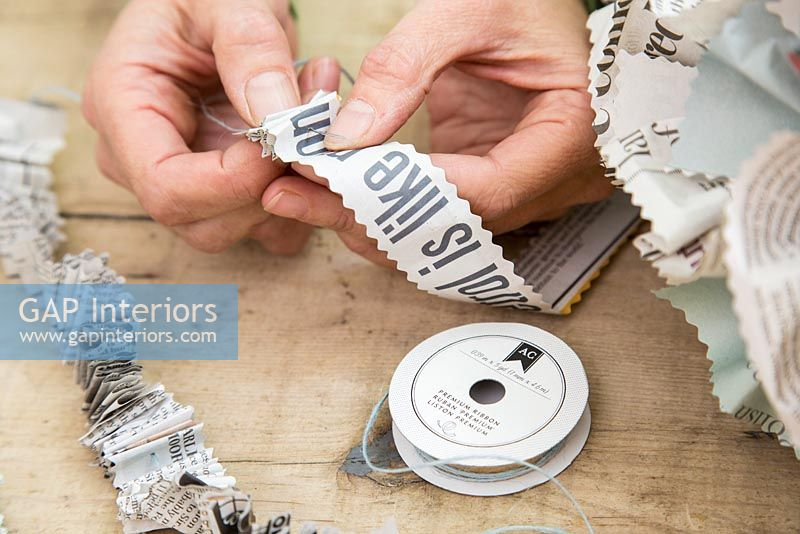 Creating a simple Christmas wreath using newspaper and  wire - threading newspaper onto string