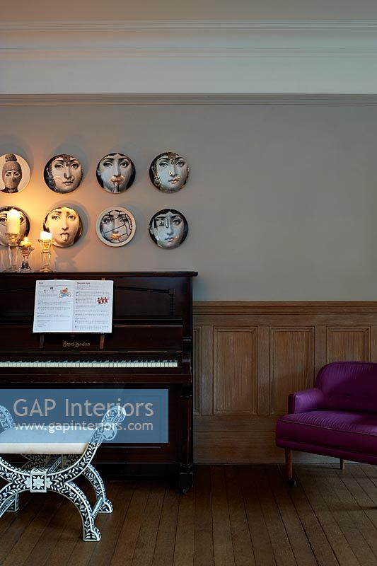 Patterned plates hung above piano
