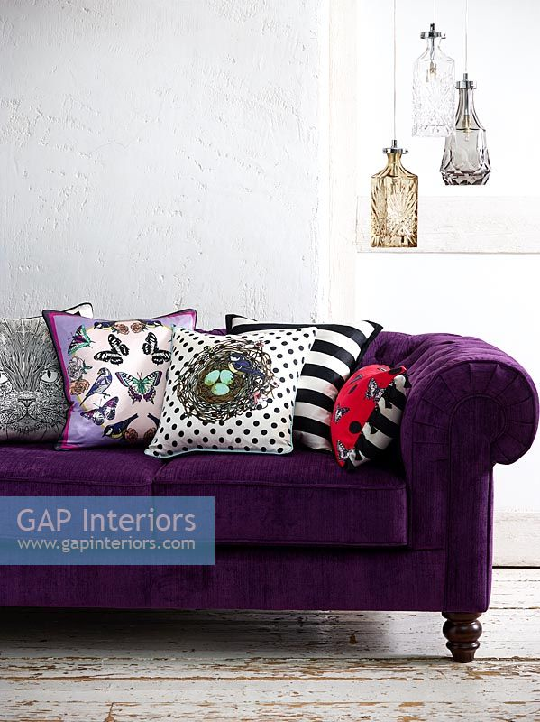 Colourful cushions on purple sofa
