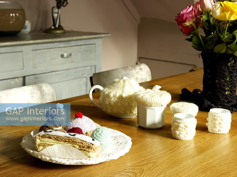 Crochet covered tableware on wooden dining table