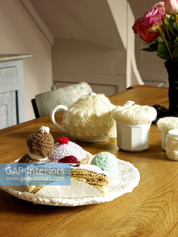 Knitted cakes on wooden dining table