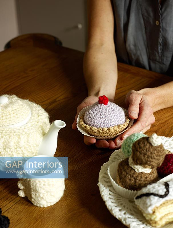 Woman holding knitted cake ornament