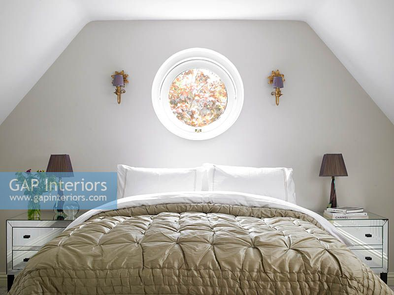 Circular window above bed
