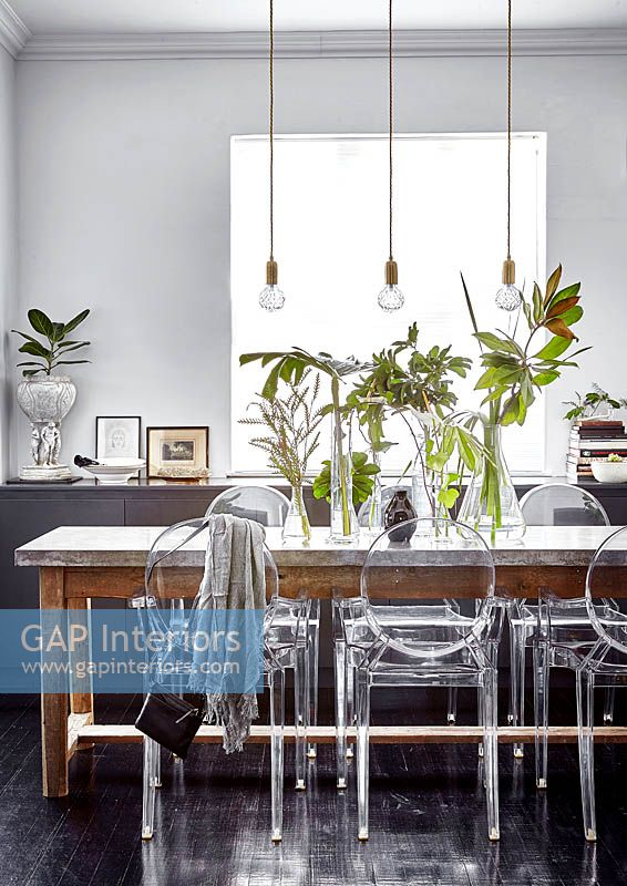 Vases of tropical foliage on dining table
