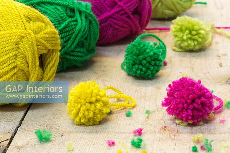 Making christmas pompom decorations - A variety of finished pompoms in different colours