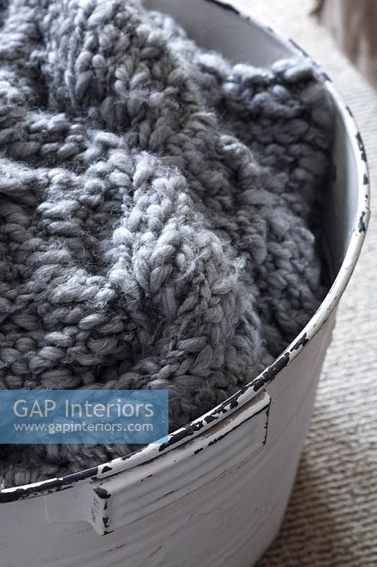 Knitted garment in white bucket