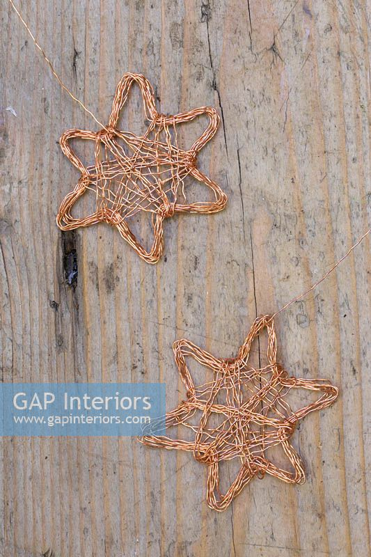 Making copper wire stars - finished decorations on wooden surface
