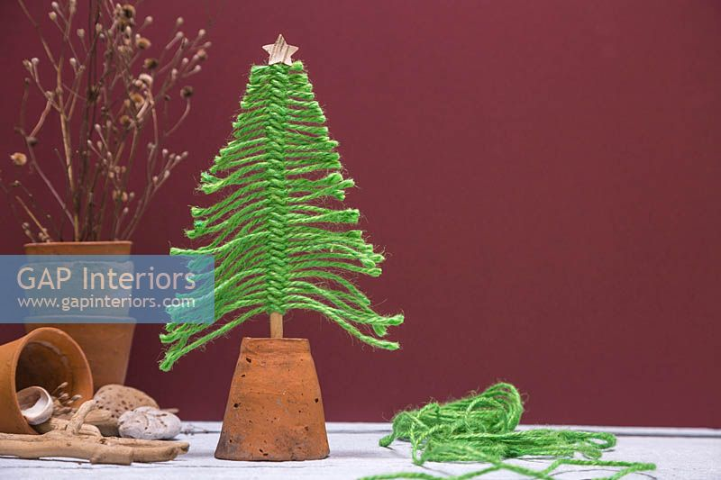 Christmas tree made from green wool mounted in an upturned terracotta pot, against a burgundy background