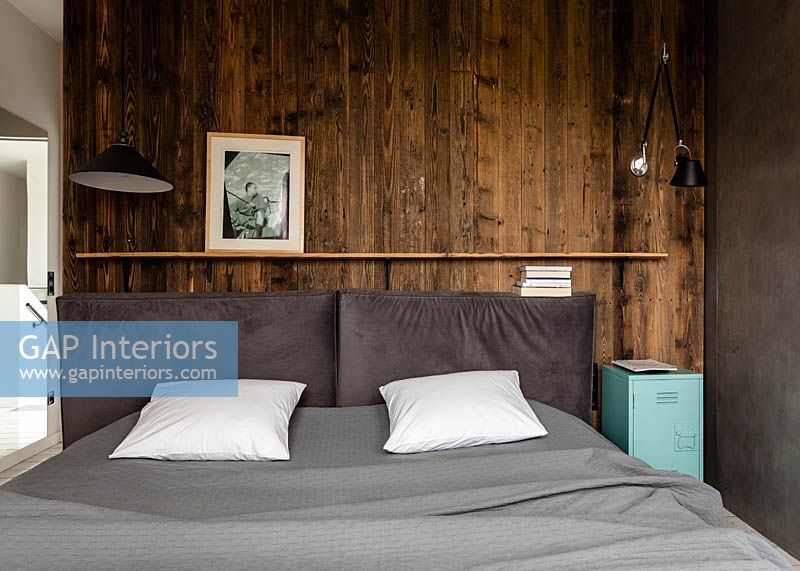 Wooden cladding behind bed