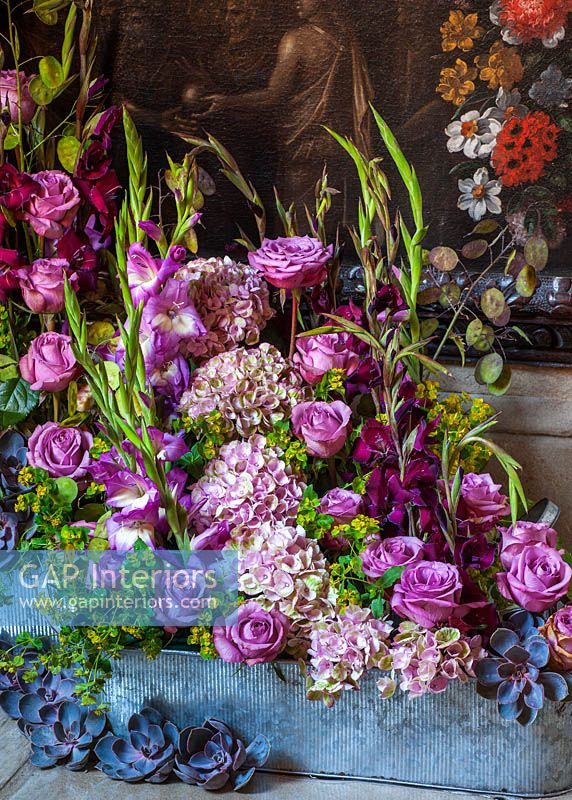 Floral display with pink Roses, Hydrangeas, Gladioli and Echeveria flowers in trough
