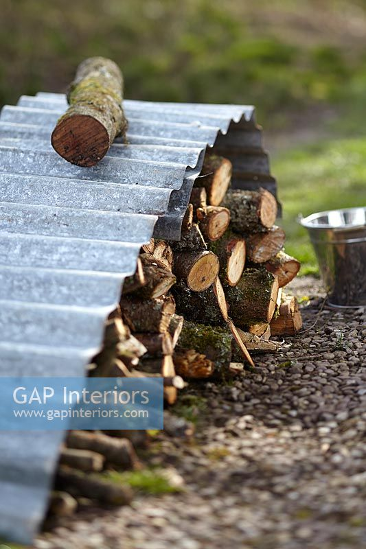 Log pile under corrugated iron sheet