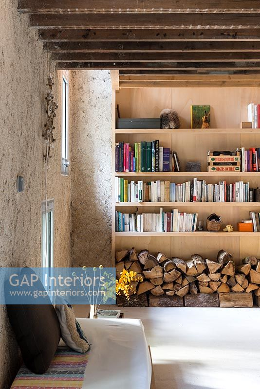 Wooden shelves and log store in living room with exposed beams