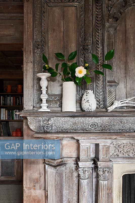Vases on carved fireplace surround