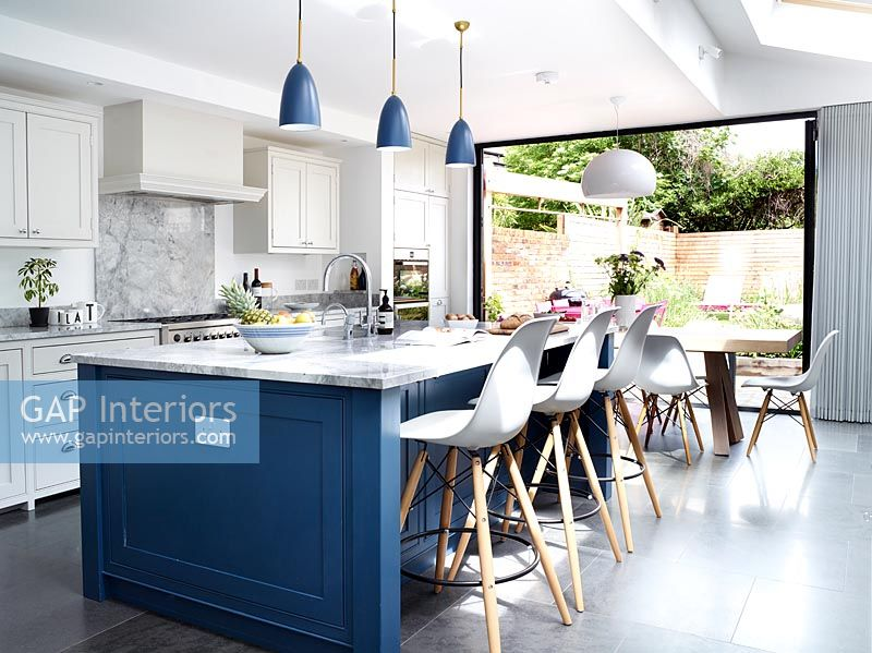 Doors in modern kitchen open to garden in summer