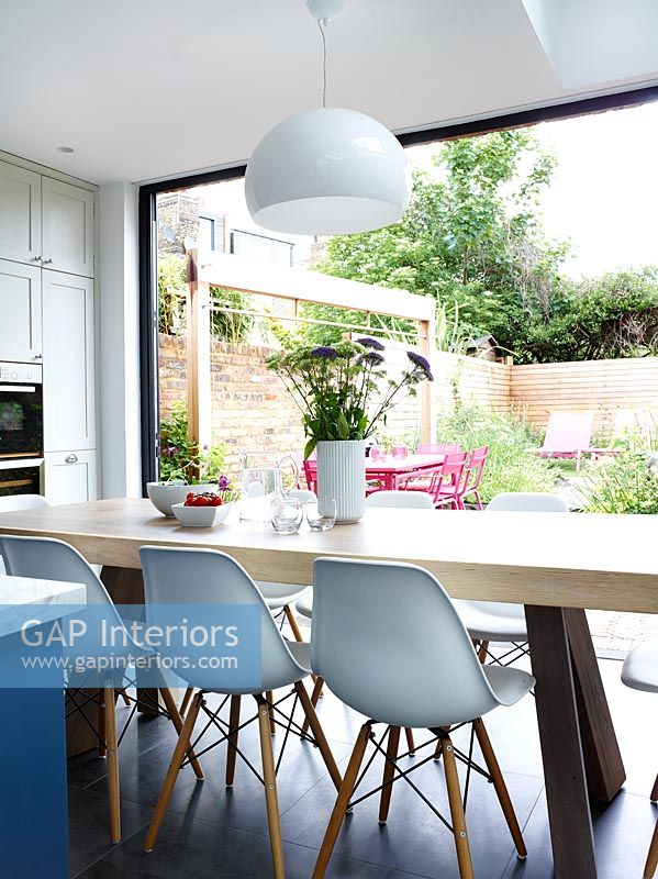 Large dining table in modern kitchen overlooking garden
