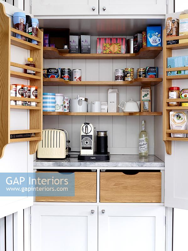 Coffee maker and toaster in modern kitchen cabinet