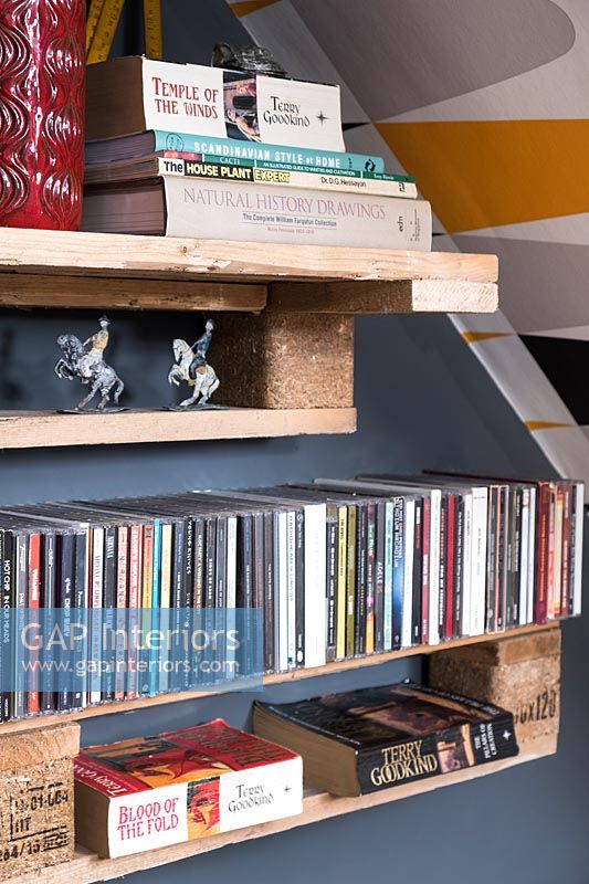 Books and CDs on wooden shelves made from pallets