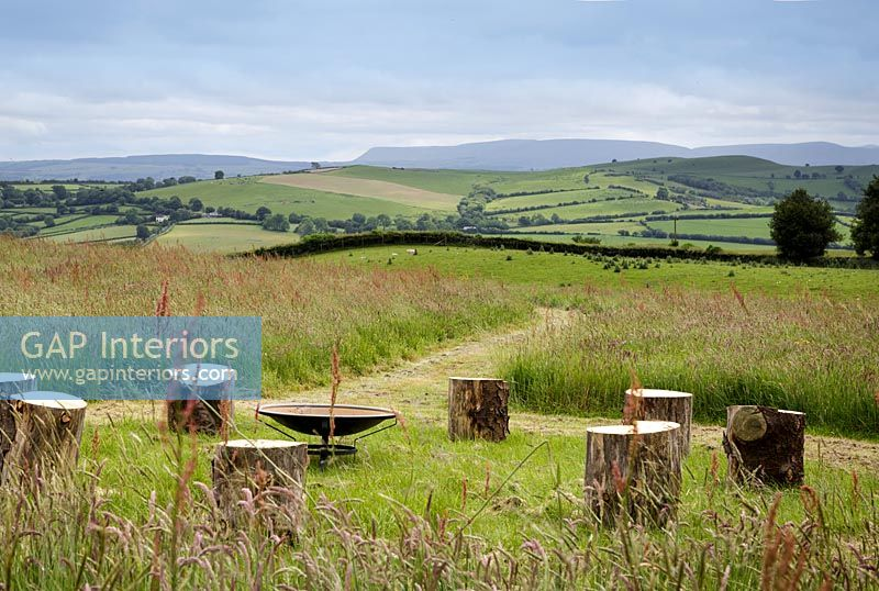 Circle of log stools around fire bowl with extensive countryside views beyond
