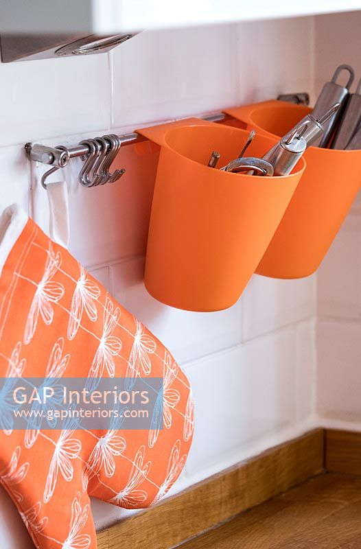 Orange cutlery holders on kitchen wall