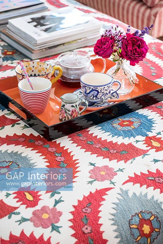 Tray for tea on modern colourful fabric covered table