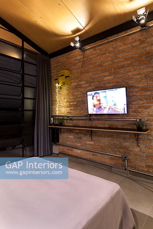 Modern industrial bedroom with wall mounted television