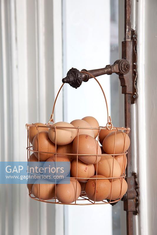 Metal basket of eggs hanging on metal handle