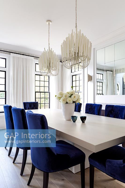 Black and white dining room with blue upholstered chairs