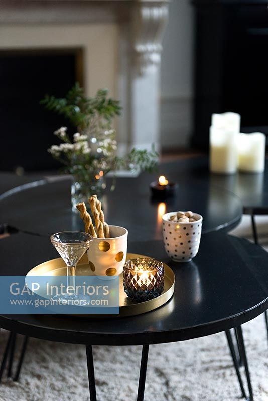 Detail of gold tray with drinks on black coffee table