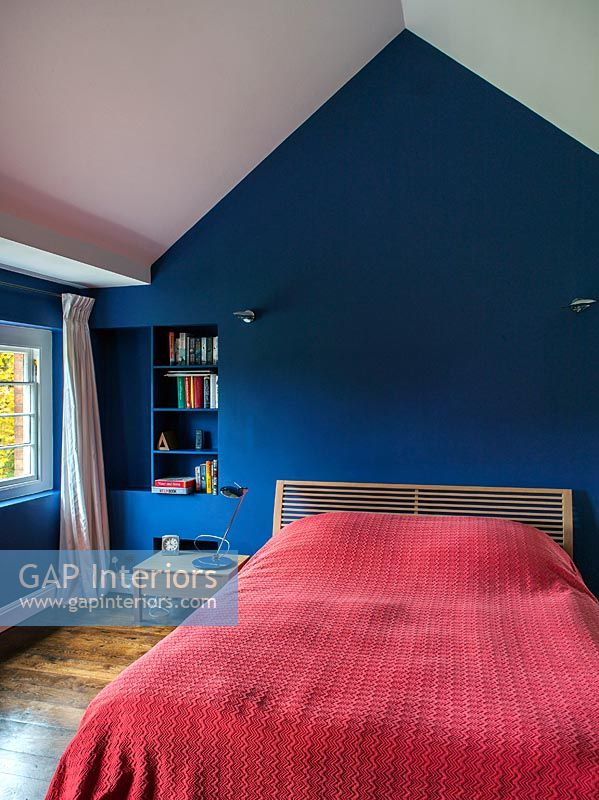Bedroom with red bedspread and blue painted walls