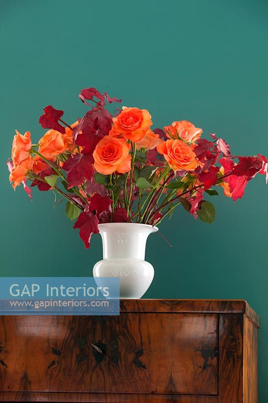 Vase of orange roses with autumn maple leaves
