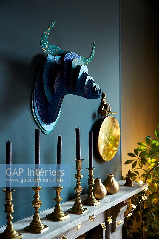 Decorative trophy head and candles over fireplace